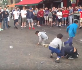 Gypsy children pick up money thrown at them by English soccer fans.