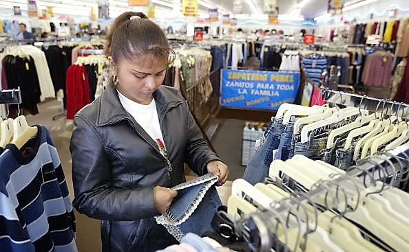 CHICAGO - OCTOBER 24: A Hispanic woman shops for clothing in a store located in Chicago's largely Hispanic Little Village neighborhood October 24, 2003 in Illinois.  (Photo by Tim Boyle/Getty Images)