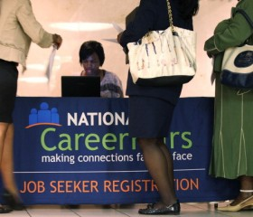 Job seekers register at the front desk during a career fair hosted by National Career Fairs