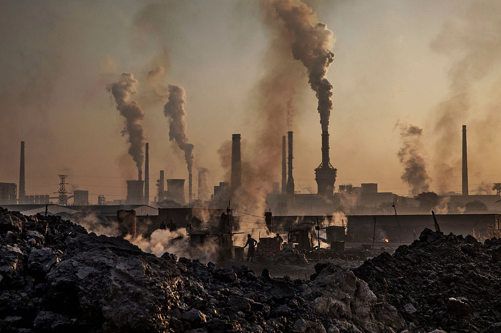 Smoke billows from a large steel plant as a Chinese labourer works at an unauthorized steel factory, foreground, on November 4, 2016 in Inner Mongolia, China.