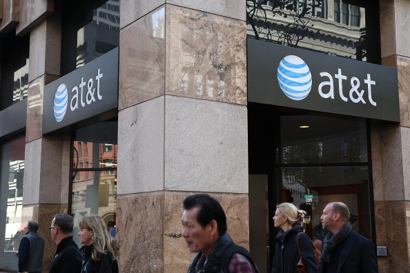 Pedestrians walk by an AT&T store on October 23, 2013 in San Francisco, California. AT&T is going to report third-quarter earnings after the closing bell.