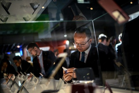 A visitor checks HTC mobile phones at the Mobile World Congress in Barcelona, Spain.