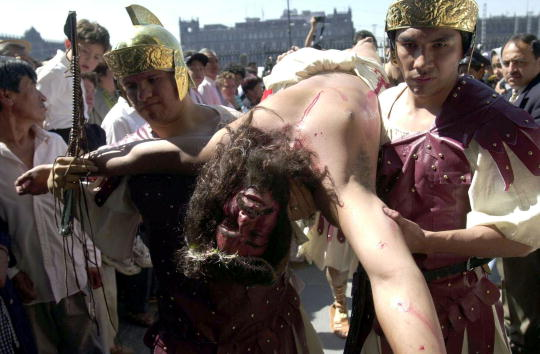 Two men dressed as soldiers carry a man portraying Jesus Christ, after his crucification, March 29, 2002 at Mexico City's Metropolitan Cathedral on Good Friday in Mexico City.