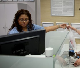 Mercedes Betaneo (L), a pharmacy technician for Walgreens, sells medicine at the Walgreens pharmacy to Christine Matthews who was using the insurance she purchased under the Affordable Care Act to buy the medicine after she couldn't renew her other insura