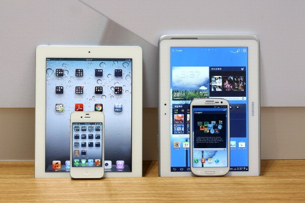 An Apple Inc. iPad 2 and iPhone 4S smartphone, left, and a Samsung Galaxy Tab 10.1 tablet computer and Galaxy S III smartphone are arranged for a photograph in Seoul, South Korea.