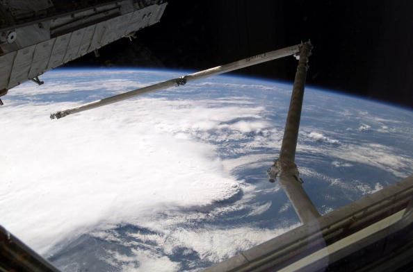 A line of thunderstorms form the backdrop for this view of the extended Space Shuttle Discovery's remote manipulator system (RMS) robotic arm while docked to the International Space Station.