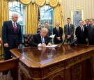 U.S. President Donald Trump signs the first of three Executive Orders in the Oval Office of the White House in Washington, DC on Monday, January 23, 2017