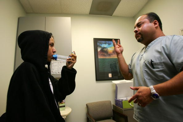An asthma patient being instructed on treatment